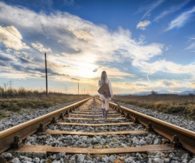 Carrying musical instrument girl walking on the tracks Stock Photo