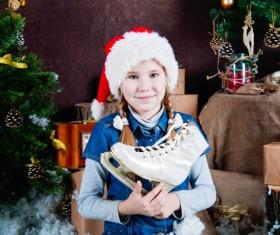 Christmas little girl holding skates Stock Photo