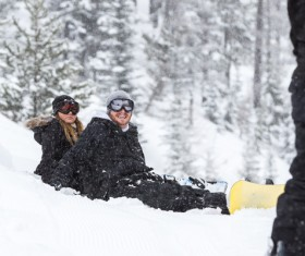 Couple sitting in the snow happy Stock Photo