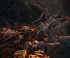 Curved road on rocky mountain landscape at dusk Stock Photo