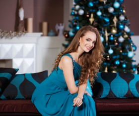 Elegant lady sitting on the couch and Christmas tree behind Stock Photo