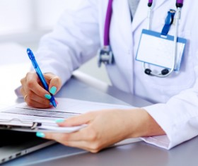 Female doctor writing medical records Stock Photo