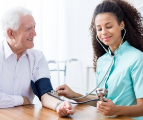 Female nurses give blood pressure elderly Stock Photo
