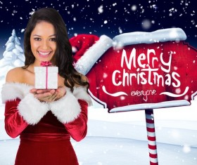 Girl holding Christmas gift and wooden sign Stock Photo