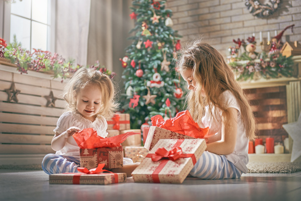 Happy sisters disassemble gift Stock Photo