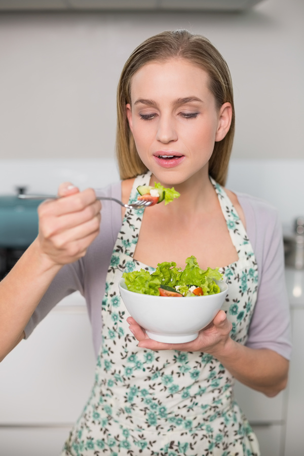 Housewife tasting salad Stock Photo