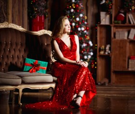 Lady in red dress sitting on sofa Stock Photo 01