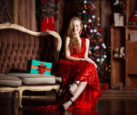 Lady in red dress sitting on sofa Stock Photo 02