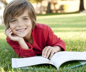 Little boy reading book lying on the grass Stock Photo