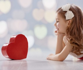 Little girl looking at heart box Stock Photo