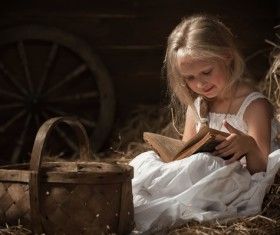 Little girl reading book sitting on haystack Stock Photo