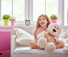 Little girl sitting in bed hugging teddy bear Stock Photo