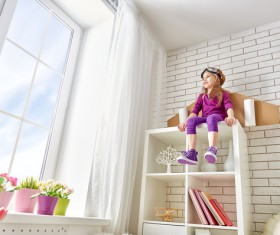 Little girl sitting on the wall cabinet Stock Photo
