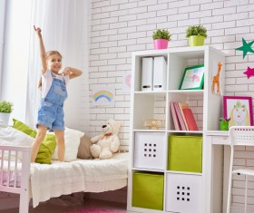 Little girl standing in bed playing Stock Photo