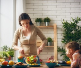 Little girl watching mother make salad Stock Photo