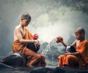 Little monk cleaning tableware in the stream Stock Photo 01