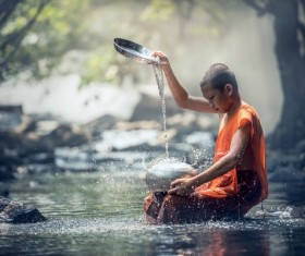 Little monk cleaning tableware in the stream Stock Photo 02