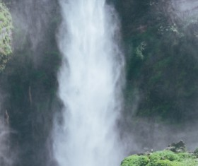 Man in front of beautiful waterfall Stock Photo