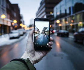 Man taking photo of cityscape with smartphone Stock Photo