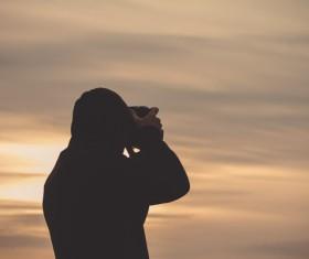 Man taking photo of sunset Stock Photo