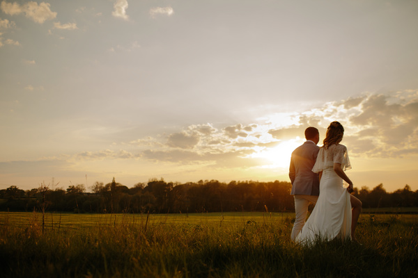 Marriage couple walking on meadow under sunset Stock Photo