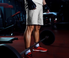 Men standing in front of the barbell Stock Photo