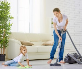 Mother and daughter clean living room Stock Photo