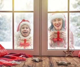 Mother and daughter holding Christmas gift outside the window Stock Photo