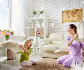 Mother and daughter holding pillows in the living room Stock Photo
