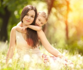 Mother and daughter sitting in the flowers Stock Photo