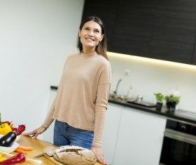 Smiling woman standing in the kitchen Stock Photo