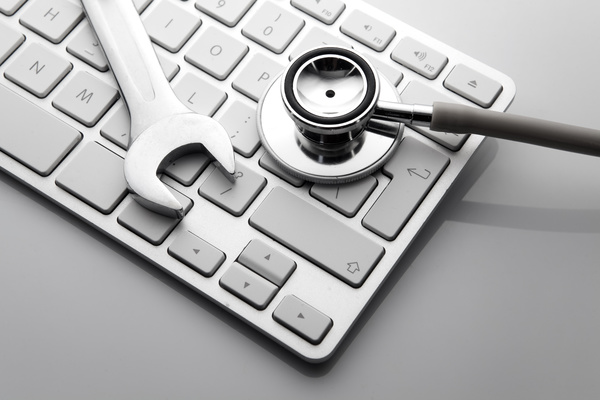 Stethoscope and wrench on the keyboard Stock Photo