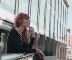 Stylish young girl relaxing outside modern building Stock Photo