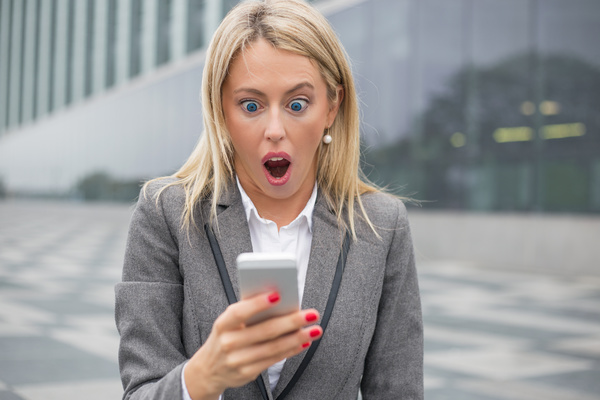 Surprised woman looking sms message Stock Photo