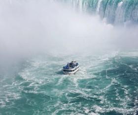 Vessel cruising on fierce waterfall Stock Photo