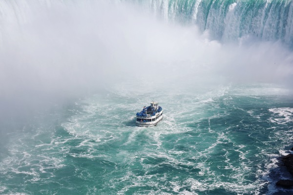 Vessel cruising on fierce waterfall Stock Photo