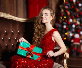 Woman in red dress sitting on the couch holding gift box Stock Photo