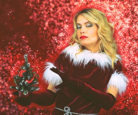Woman wearing christmas costume holding christmas tree Stock Photo