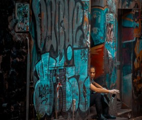 Young man resting near dirty painted wall Stock Photo