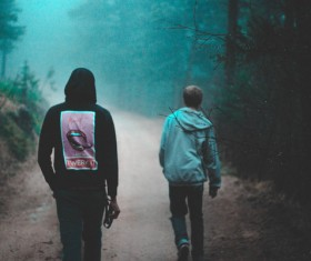 Young men walking on misty pathway Stock Photo