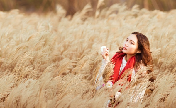 Young women holding flower at meadow in summer morning light Stock Photo
