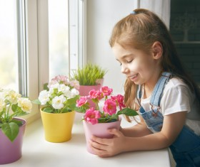 little girl looks at the flowers on the windowsill Stock Photo