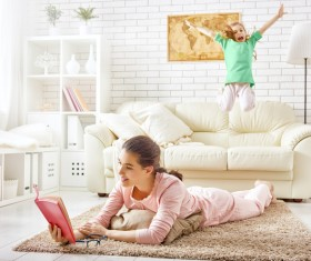 living room reading book mother and daughter playing on the couch Stock Photo