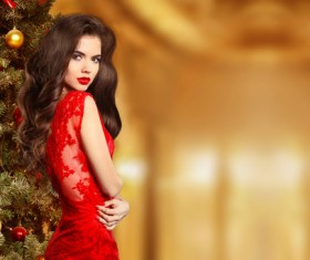 woman in red dress standing by the Christmas tree Stock Photo