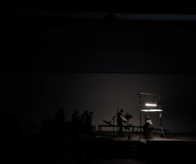 Artists performing on dark stage Stock Photo