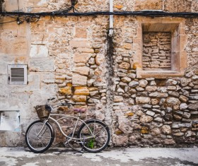 Bicycle leaning against old brick house Stock Photo