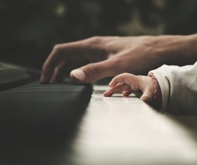 Closeup father and baby playing piano Stock Photo