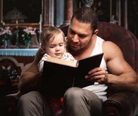 Dad reading book with her daughter Stock Photo