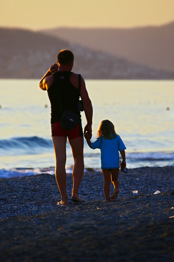 Father and daughter walking on the beach Stock Photo