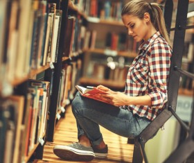 Female student reading book in the library Stock Photo